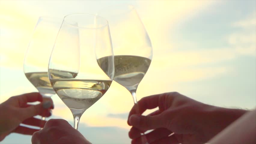 People holding Glass of Wine, Making a toast over Sunset sky. Birthday. Friends drinking White Wine, toasting. Clink. Party outdoors. Enjoying time together. Slow motion 240 fps 4K UHD video