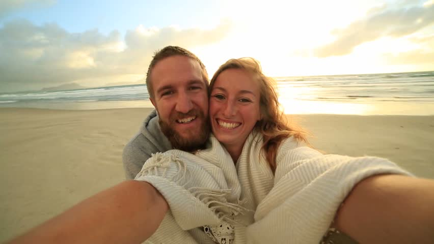 Self portrait of happy young couple on beach at sunset Cheerful young couple by the sea take a selfie portrait using a mobile phone. | Shutterstock HD Video #28761835