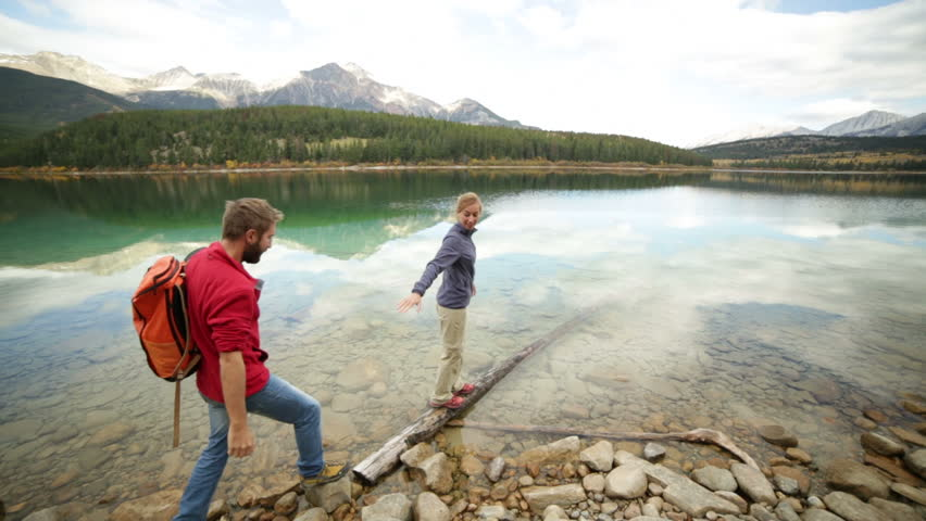 Young woman walking on log above lake giving helping hand to partner to join. People travel and helping hand concept | Shutterstock HD Video #28761859