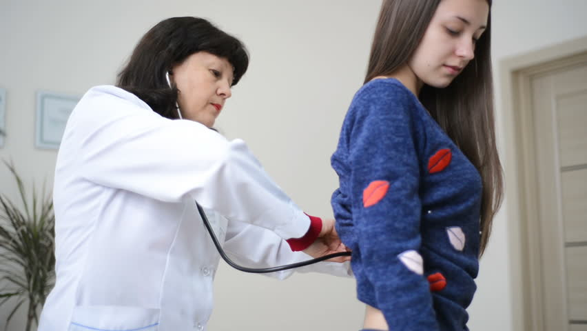 Doctor checking or examining ausculting lungs on back of young female patient with stethoscope | Shutterstock HD Video #28764769