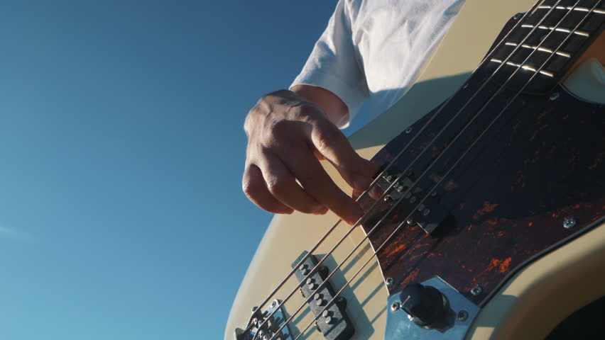 The man play the bassguitar outdoor by picturesque sunset and sky background. Slowmotion.