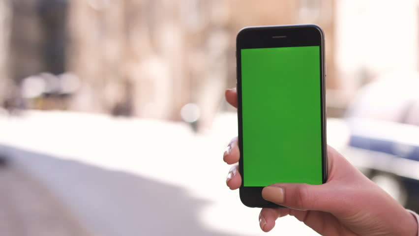 Closeup of woman hands holding phone with green screen vertically to the streets | Shutterstock HD Video #28789693