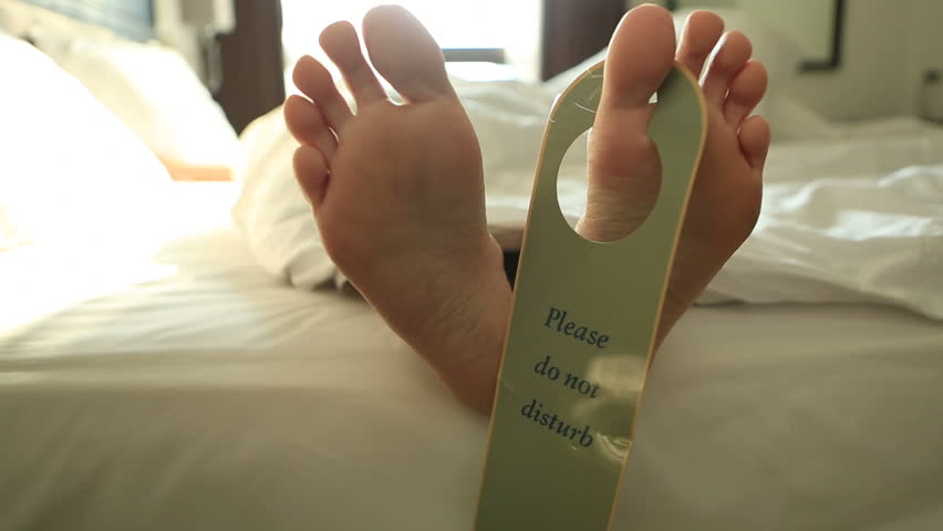 Human's feet on bed with 'do not disturb' sign Happy feet of a person laying down in a comfortable bed in an hotel room with the sign 'do not disturb' hanging on them. #28801891
