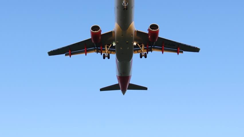 Airplane Flying Overhead against Blue Sky - Taking Off / Landing
