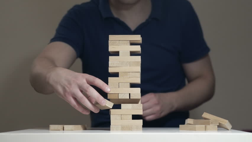 Timelapse loop of assembilng and disassembling Jenga Tower. IT man is playing Jenga game and disassembling the tower. Taking bricks out one by one and putting them back together. Perfect Skills. Royalty-Free Stock Footage #28812235