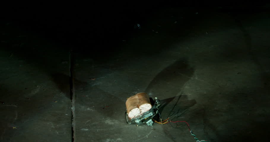Airbag Inflation Isolated - A white airbag bursts open in a dark room, and the force causes it to rise up off of the floor