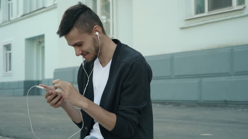 Smiling young man in the street — looking at the camera. Browsing smartphone, listening to the music. People stock footage shot at summer season time. | Shutterstock HD Video #28828060
