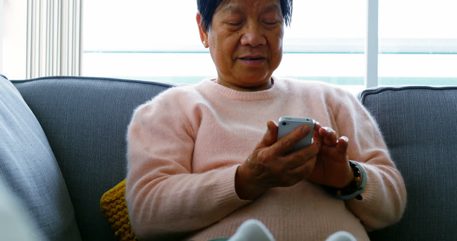 Senior Asian woman using mobile phone in living room at home #28846849
