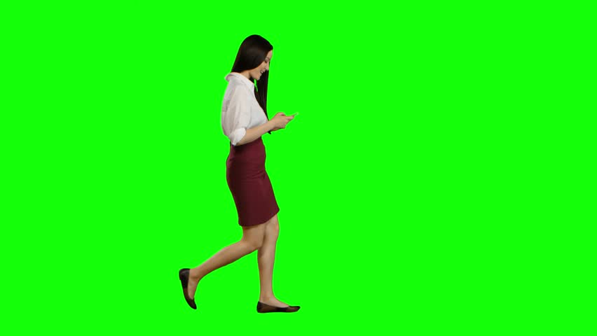 Girl of asian appearance walks the street, the phone looks at interesting pictures. Green screen