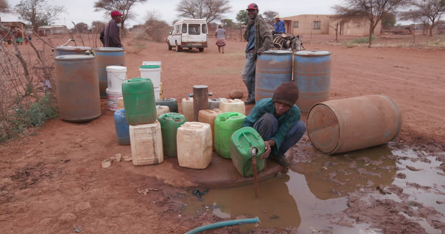 Poor people in Africa unable to maintain social distance due to water crisis. People collecting water in containers from a communal tap due to severe drought in South Africa