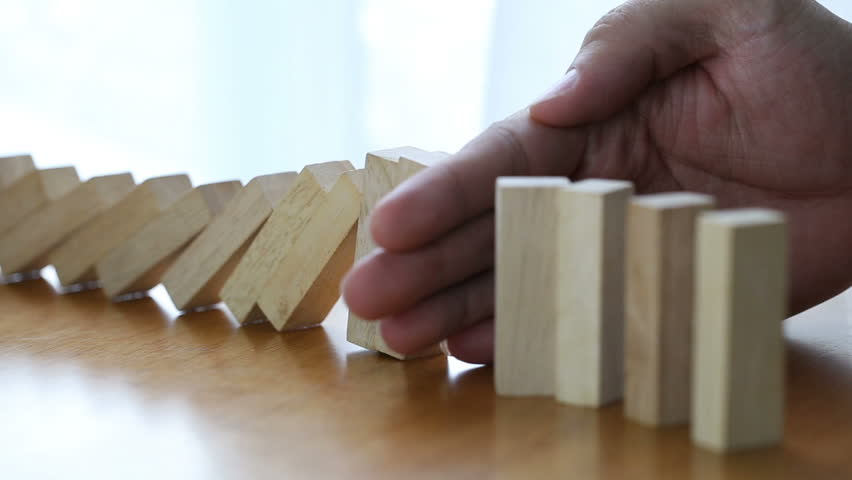 Male hand stopping the domino effect. Risk control concept  | Shutterstock HD Video #28859857