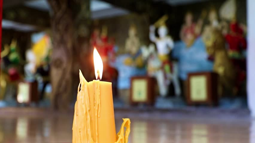 Flame of the yellow candle inside Buddhist temple. Burning large candles, on background statues in Buddhist monastery. | Shutterstock HD Video #28863487