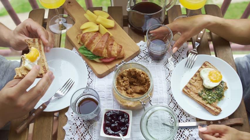?ouple having Breakfast on the balcony. Couple eats toast and drinks coffee | Shutterstock HD Video #28865053