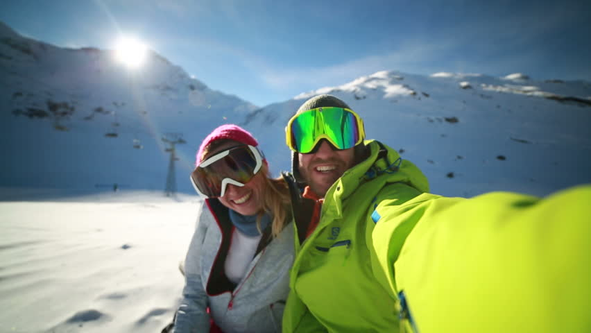 Couple taking selfie on ski slope Young couple takes selfie on ski slopes, Swiss Alps