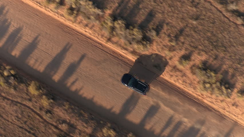 AERIAL: Black SUV car driving along the empty dusty road trough dry meadow desert valley in Utah on sunny morning. Flying above jeep traveling on straight dirt route into Capitol Reef at golden sunset
