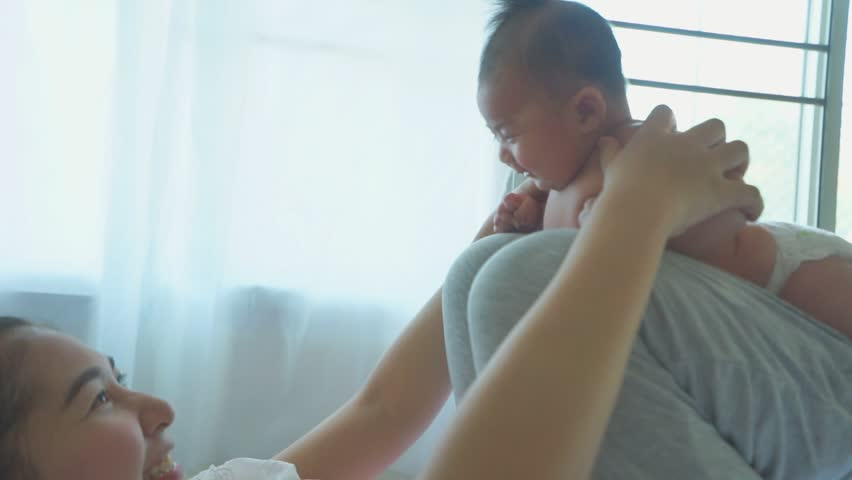 asian young pretty mother kissing her little baby with love #28881202