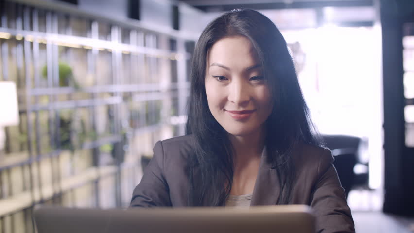 PAN of smartly dressed Asian businesswoman sitting in cafe on sunny day and typing on laptop while smiling   Shutterstock HD Video #28882120