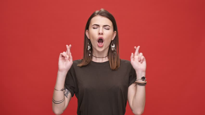 Young worried girl standing with fingers crossed for good luck and wins isolated over red background | Shutterstock HD Video #28893670