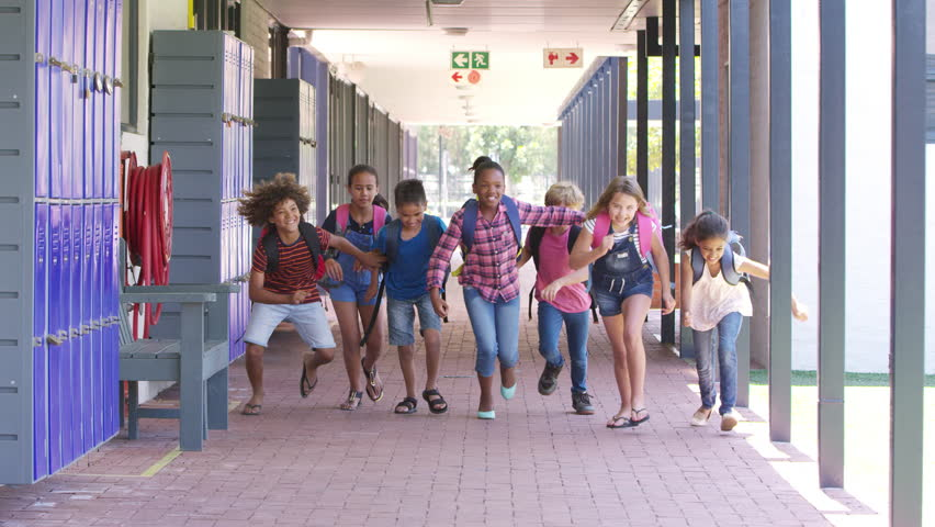 Kids running to camera in school hallway, front view