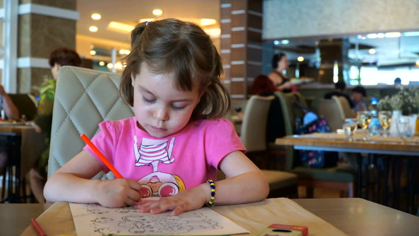 Girls of European appearance, 4-5 years old, sit in a restaurant and draw with pencils. Around her people walk, sit at tables and eat. #28907350