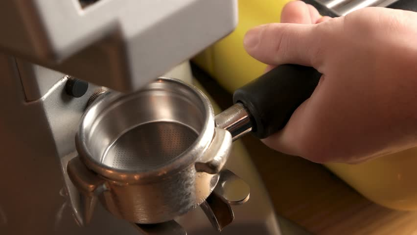Male hand and coffee grinder. Portafilter with ground coffee.   Shutterstock HD Video #28916812