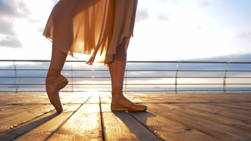 Close up of a ballet dancer's feet as she practices in pointe exercises on the embankment near sea, sunrise background,Woman's feet in pointe shoes. Ballerina shows classic ballet pas.Slow motion. #28922884