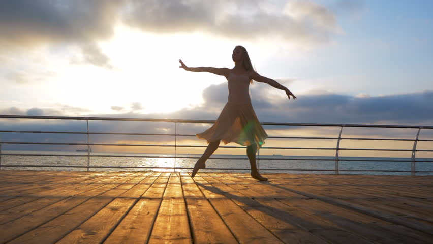 Dancing ballerina in beige silk dress and pointe on embankment above ocean or sea at sunrise or sunset. Silhouette of young woman with long hair practicing classic exercises with emotions.SLOW MOTION.