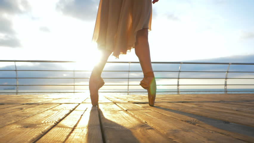 Close up of a ballet dancer's feet as she practices in pointe exercises on the embankment near sea, sunrise background,Woman's feet in pointe shoes. Ballerina shows classic ballet pas.Slow motion. #28923016