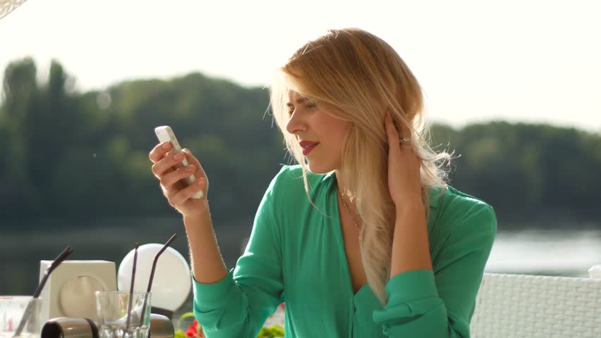 Smiling blonde girl with iPhone in cafe