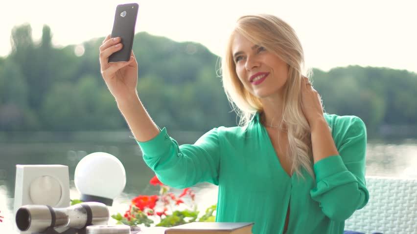 Modern beautiful girl makes selfie in cafe