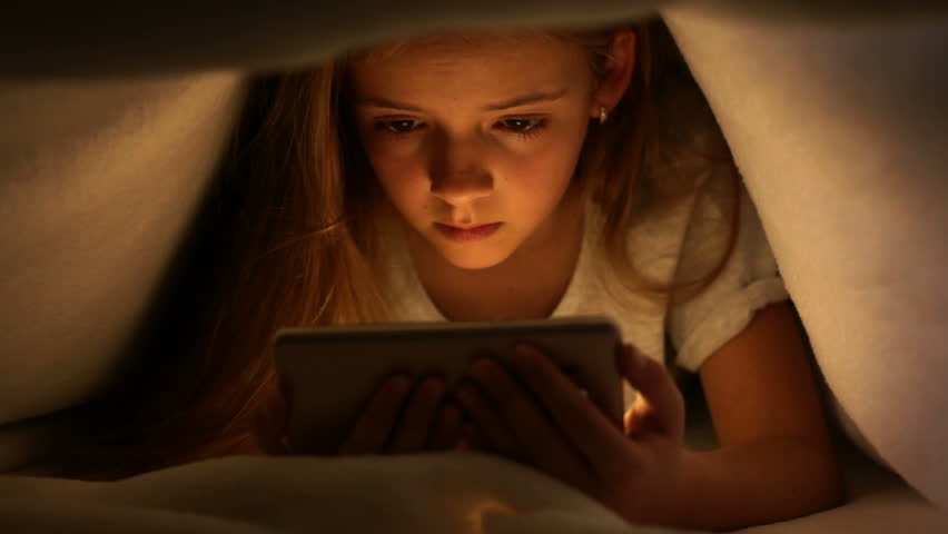 Young girl watching online content on her smartphone at night - hiding under the blanket, static camera | Shutterstock HD Video #28925431