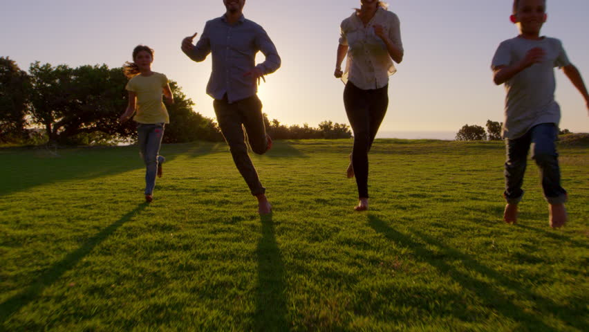 Young white family running towards moving camera in a park #28929829