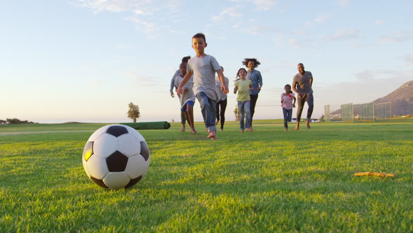 Two families playing football in park