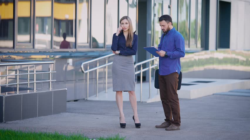 Business people are working outside. Female sales manager standing near office speaking on the telephone. Man dressed in blue shirt and brown trousers is listening to businesswoman and making notes. | Shutterstock HD Video #28931935