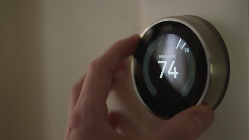Man Adjusting Smart Thermostat Gadget Settings At Home #28941742