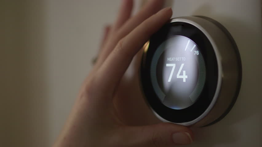Woman Adjusting Smart Thermostat Gadget At Home #28941796