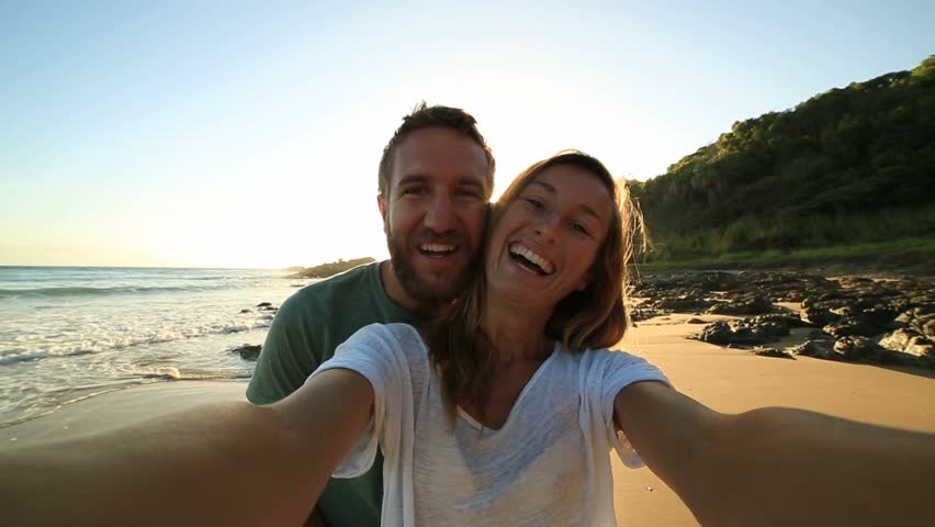 Cheerful young couple on the beach take a selfie portrait at sunrise. Shot in Australia People enjoying vacations concept