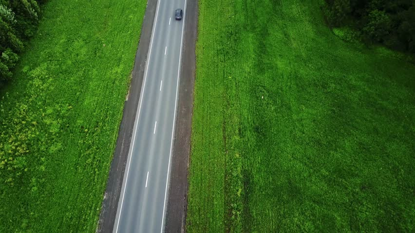 Delivery trucks driving towards the sun. Aerial view 0f green fields and trucks