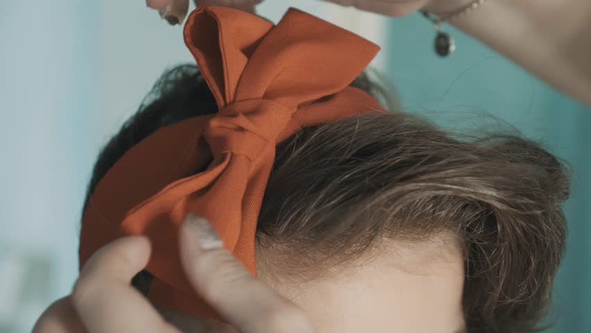 SLOW MOTION: Caring mother ties a red bow on her daughter's head, creating a beautiful hairstyle. High Angle. Extreme Close Up. Female hands tie a red bandage on the head. Child with curly hair