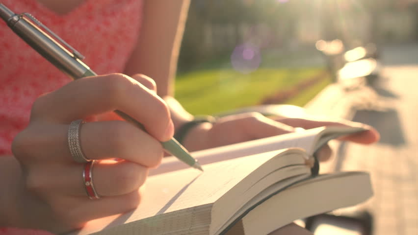 Looking up for inspiration while walking outdoor in green spring park garden. Close-up of young woman hands writing down her hopes and dreams of future into her diary, making plans. Planner To Do Royalty-Free Stock Footage #28954279