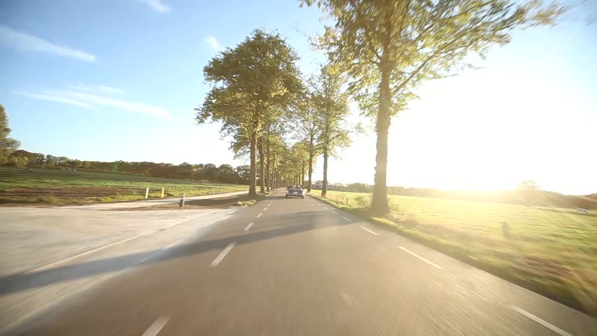 video footage of a on-board camera on a car driving on a country road in the sunset #2895772