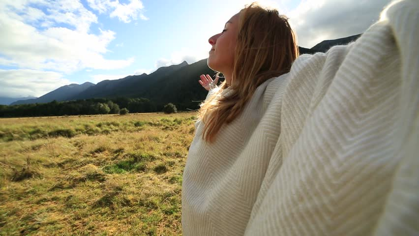 Cheering young woman relaxing in the morning sunlight, arms outstretched Shot on the South Island of New Zealand    Shutterstock HD Video #28958140
