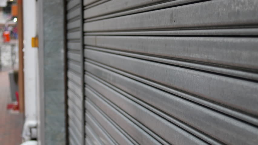 A steady close up shot of a bakery store closing its steel roller doors.