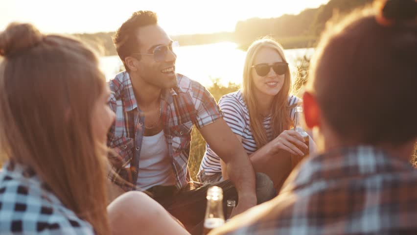 A company of four young friends having a picnic by the river, they are chatting, laughing, drinking beer. Casual wear, summertime, bright light of the sunset. Being happy, young and free. #28972513