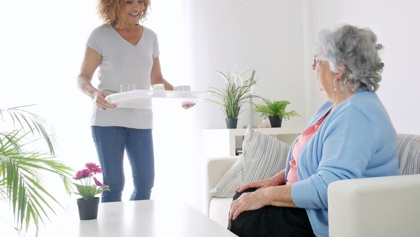 cheerful mature woman serving breakfast and taking care of a elderly senior woman at home