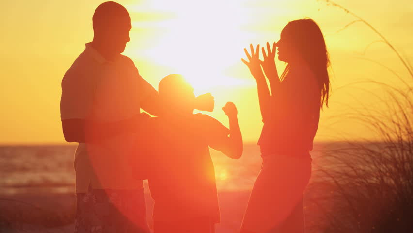 Silhouette of active ethnic family having fun and enjoying togetherness on the beach at sunset RED EPIC #28979479