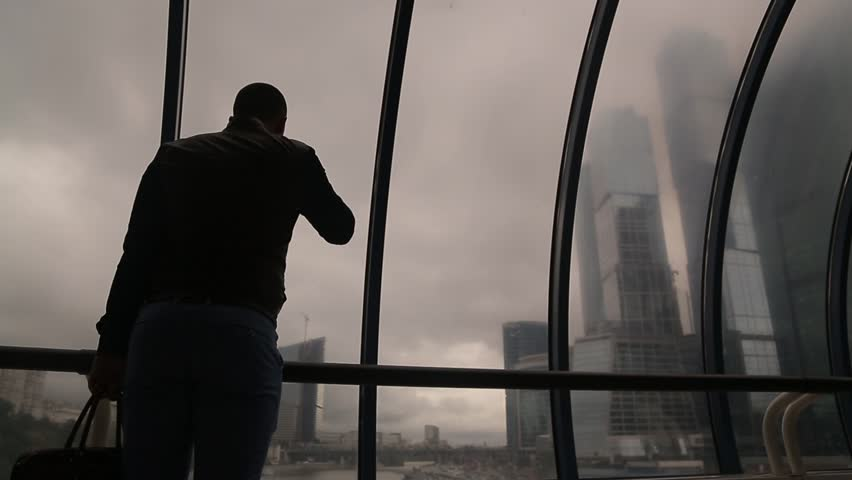 Man with briefcase drinks coffee looking at Moscow City towers at bridge static camera medium shot | Shutterstock HD Video #28981744