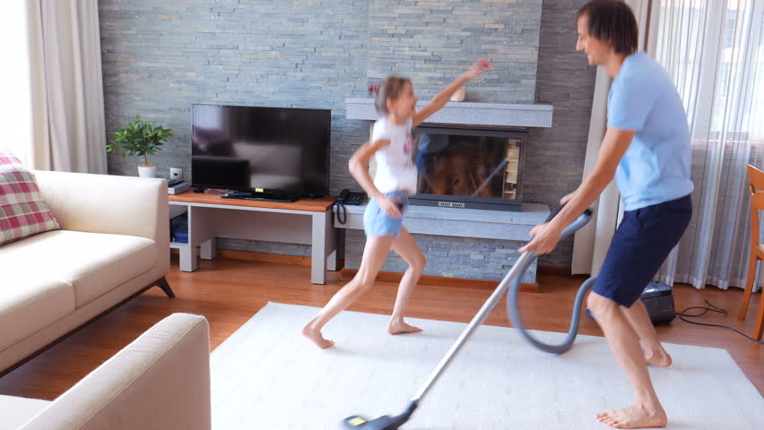 A happy family. Dad and daughter having fun in a clean house. A man is dancing with a vacuum cleaner.