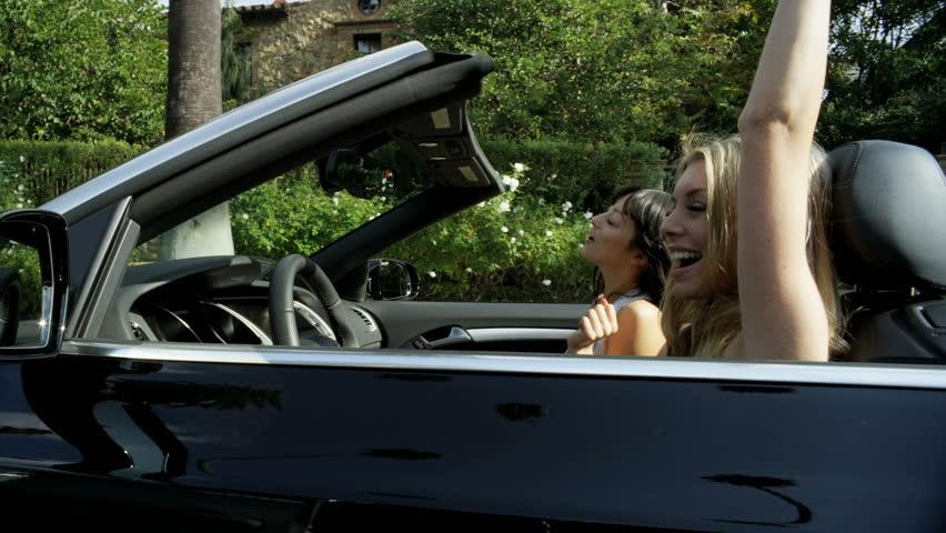 California, USA - April 2017: Beautiful young European friends tossing hair dancing and singing enjoying summer sun in luxury open top car | Shutterstock HD Video #28983622