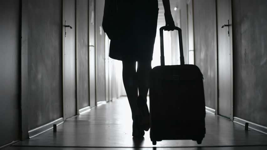 Tracking with low-section of silhouette of elegant woman in skirt and high heels shoes carrying suitcase and walking along hallway of hotel towards her room; black and white slow motion shot   Shutterstock HD Video #28997305